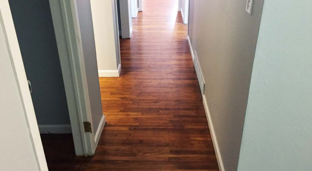 A hallway with refinished hardwood floors by Bob